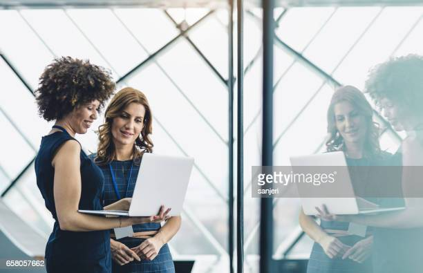 Two Businesswomen Working in The Office, Using Laptop