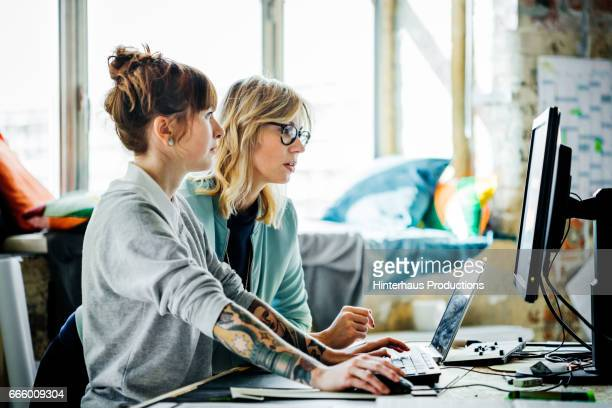 two businesswomen working on a computer - geschäftsgründung stock-fotos und bilder