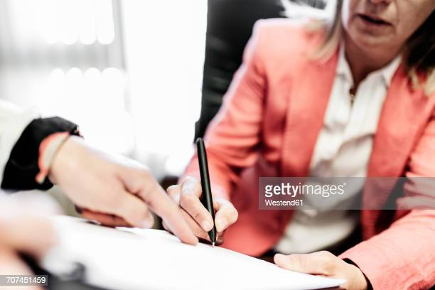 Two businesswomen working on document in office