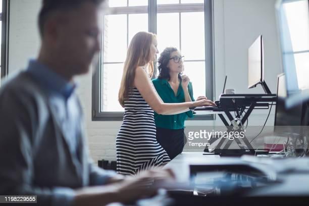 スタンディングデスクで働く2人のビジネスウーマン。 - 人間工学 ストックフォトと画像