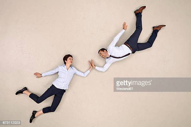 two bussiness colleagues flying and high fiving - hovering stock pictures, royalty-free photos & images
