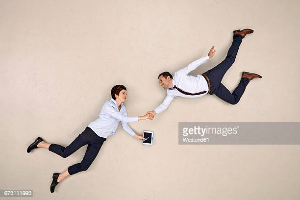two bussiness colleagues flying and shaking hands - beige background stock pictures, royalty-free photos & images