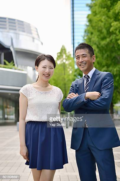 Two busuiness people standing outside building