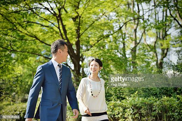 Two busuiness people walking in urban park
