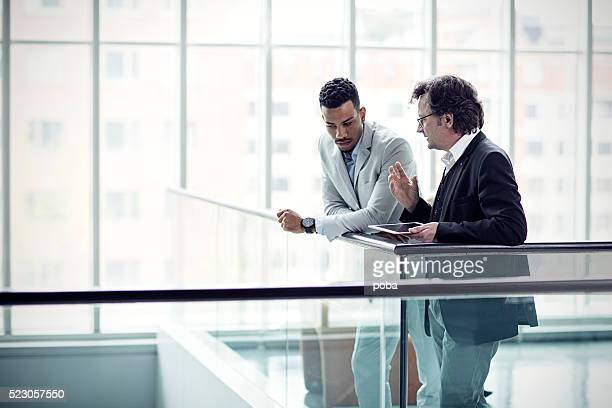 two busuinessmen having a casual talk in hall - face to face stock pictures, royalty-free photos & images