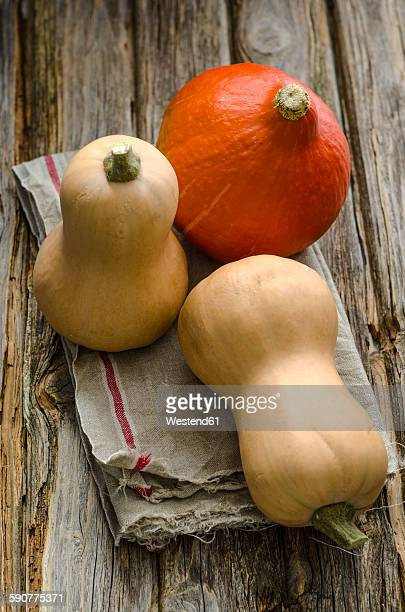 Two butternut squashes and a Hokkaido pumpkin on cloth and wood