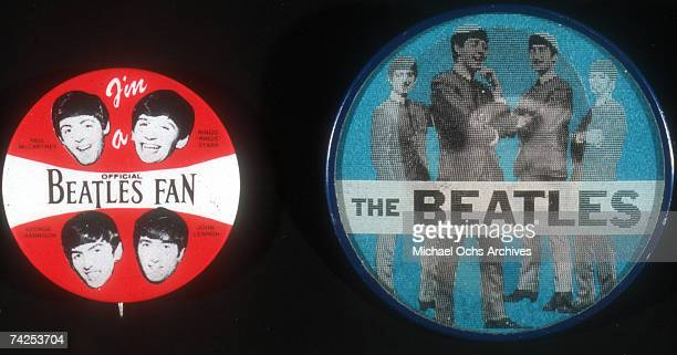 Two buttons which are memoribilia of rock and roll band 'The Beatles' featuring pictures of the band