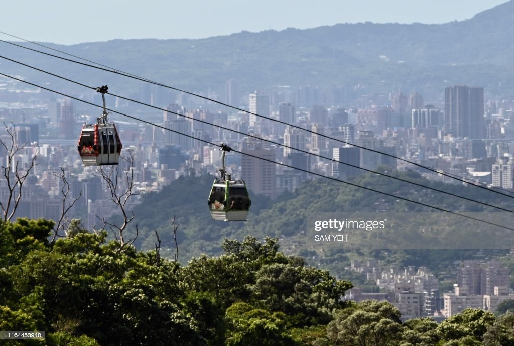 Two cable cars move in the air between Maokong and Taipei