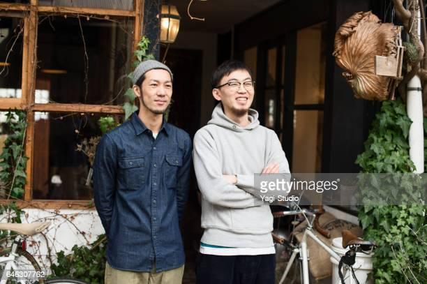 喫茶店の前に2人のカフェオーナーが立っていた。 - ショッピングエリア ストックフォトと画像