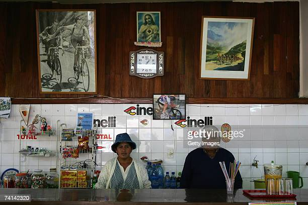 Two cafeteria workers pose in front of a photograph of Faustino Coppi and a painting of the Tour de France at the Alto Irpavi Velodrome May 13 2007...