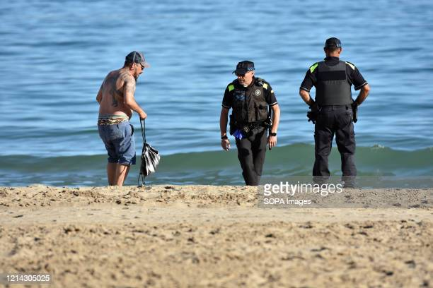 Two Calafell local police officers talk to a man on the beach as they patrol during the final confinement of Phase One Calafell is in Phase One of...