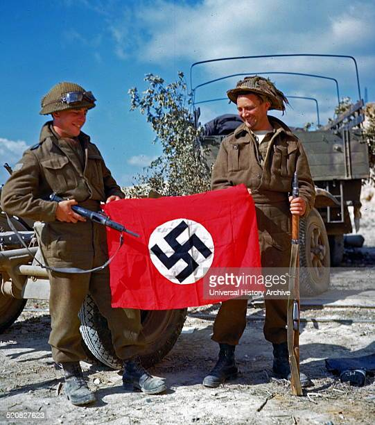 Two canadian soldiers hold a Nazi flag which they captured in a French quarry just south of Hautmesnil Dated 1944