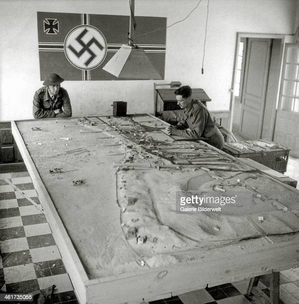 Two Canadian soldiers look at a German model of the area around Widerstandsnest 29 and the mouth of the Seulles as well as Widerstandsnest 31 . June...