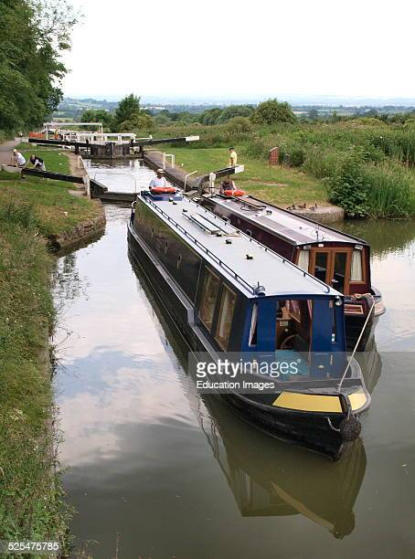Two canal boats breasting up where two narrow boats are tied together so one boat runs their engine and steers The Kennet and Avon Canal Devizes...