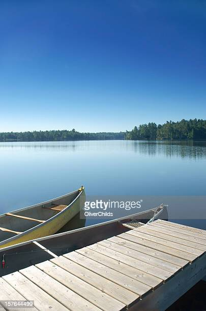 two canoes docked on a still lake. - moored stock pictures, royalty-free photos & images
