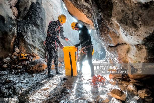 渓谷の底にある防水丈夫なバッグにクライミングロープを集める2人のキャニークライマー - ポリマー ストックフォトと画像