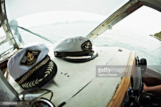 two captain's hats resting on the dashboard of a motorboat, avacha bay, russia - sailor hat stock pictures, royalty-free photos & images