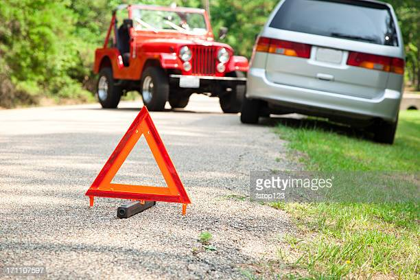 Two car accident with focus on orange triangle warning sign.