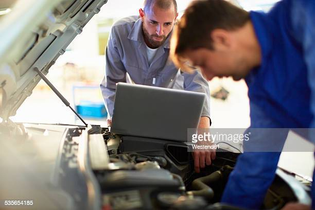 two car mechanics at work in repair garage - mechatronics stock pictures, royalty-free photos & images