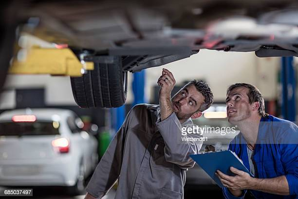 two car mechanics in a workshop examining car together - hoisting stock pictures, royalty-free photos & images