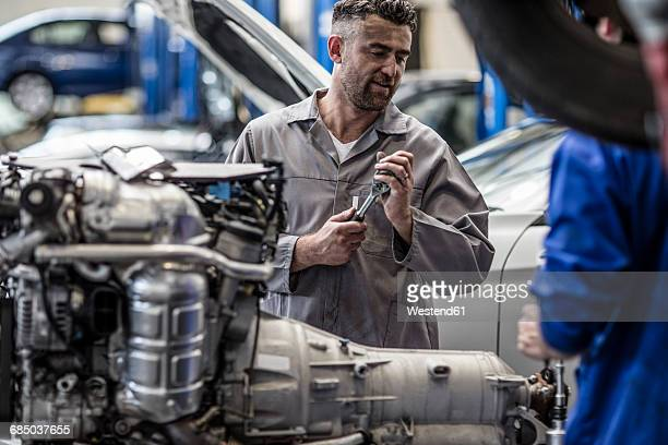 two car mechanics next to v8 engine in a workshop - v型8気筒 ストックフォトと画像