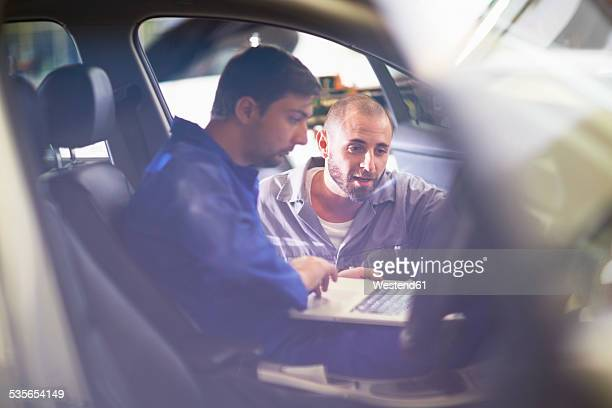 two car mechanics with laptop in repair garage - mechatronics stock pictures, royalty-free photos & images
