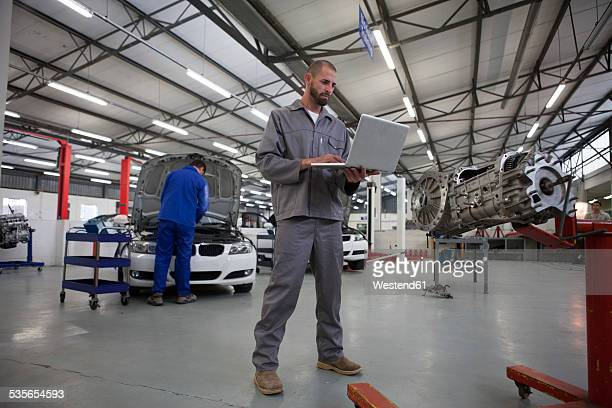Two car mechanics with laptop in repair garage