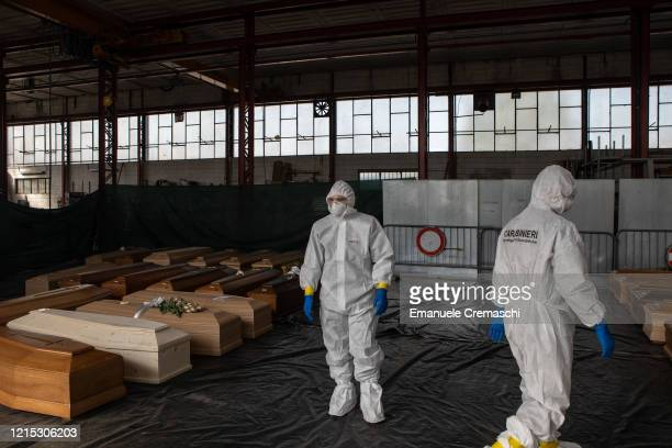 Two Carabinieri officers wearing protective suits stand inside a warehouse used to stock coffins on March 28 2020 in Ponte San Pietro near Bergamo...