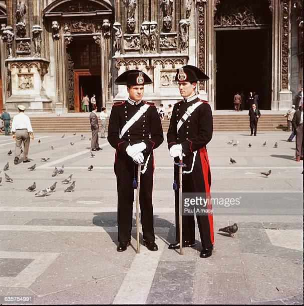 Two carabinieri or Italian police stand in front of an old building in Milan Italy ca 19501980