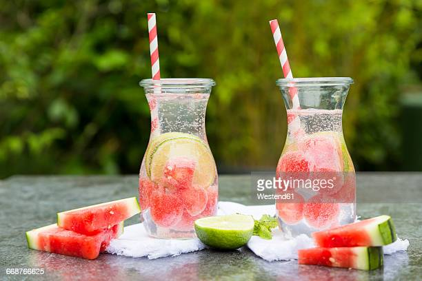 Two carafes of infused water with watermelon and lime