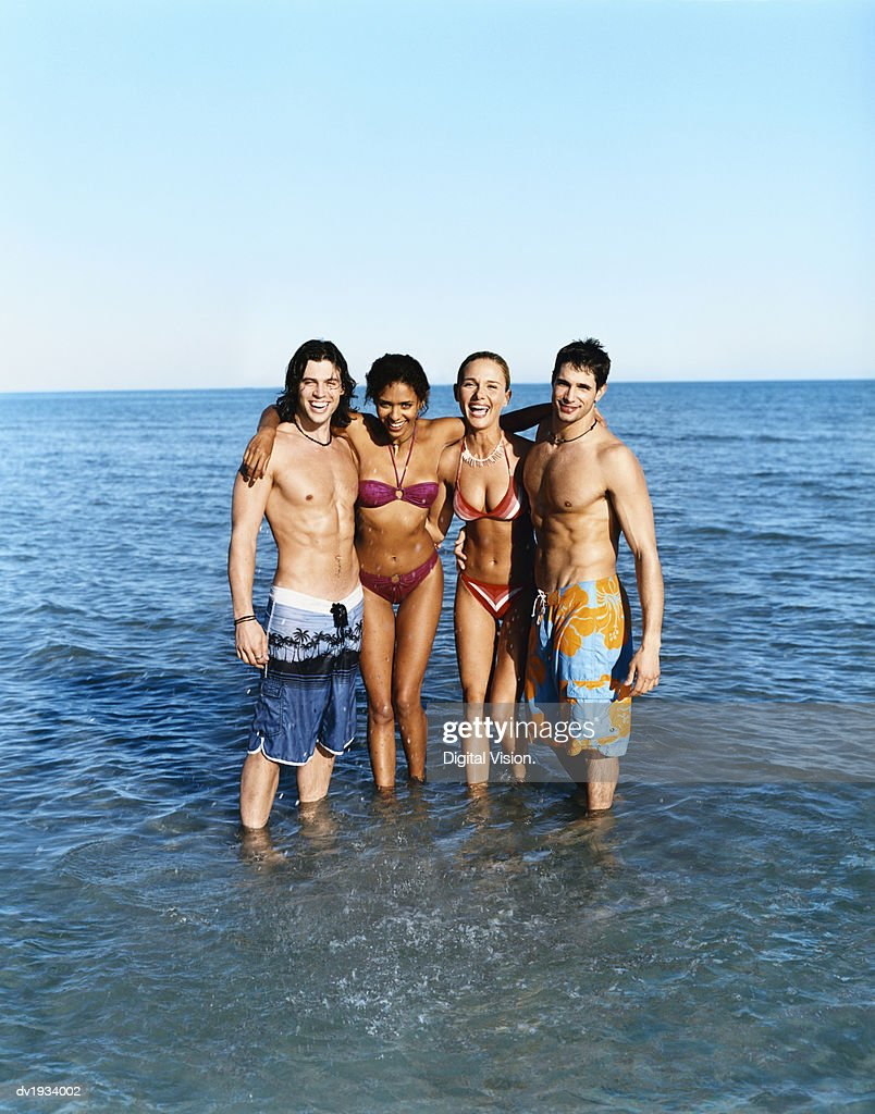 Two Carefree Couples on Holiday Standing in Shallow Water : Stock Photo