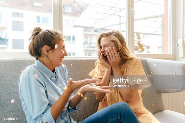 two carefree young women sitting on couch - laughing stock pictures, royalty-free photos & images