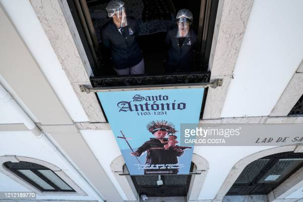 Two caregivers stand at a window of Santo Antonio retirement house in Figueira da Foz, on May 7, 2020. - The management of two retirement homes in...