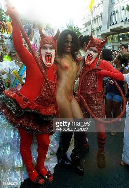 Two carnival participants disguised as devils are dancing samba with a naked transvestite during the traditional parade of the Banda Carnavalera...