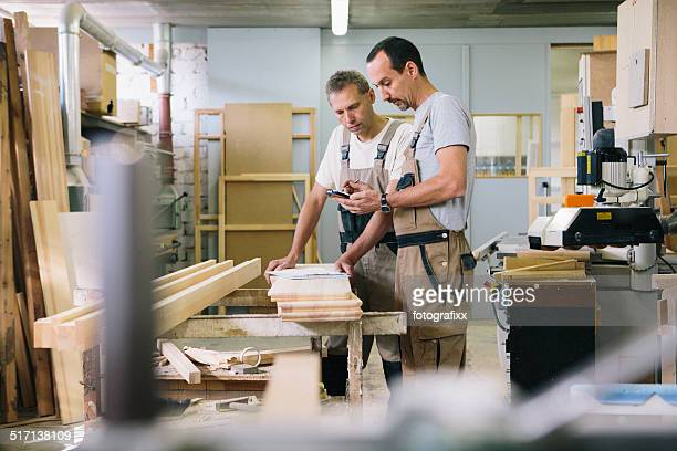 two carpenter using smart phone for planning