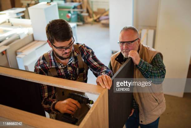 two carpenters install a furniture door - professional occupation photos et images de collection