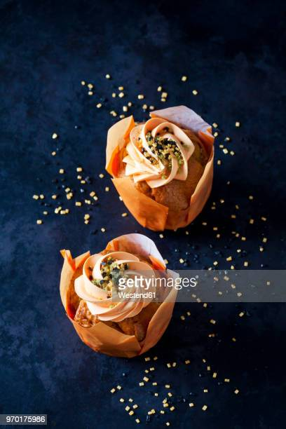 Two carrot cup cakes garnished with  cream topping and sugar granules