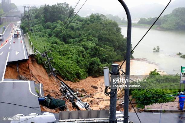 Two cars are involved in a landslide triggered by heavy rain on July 6, 2018 in Iizuka, Fukuoka, Japan. At least one person was killed and evacuation...