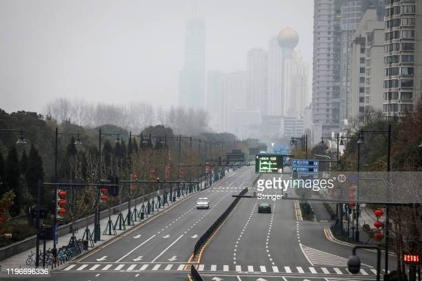 Two cars drive on an empty road on January 27 2020 in Wuhan China As the death toll from the coronavirus reaches 80 in China with over 2700 confirmed...