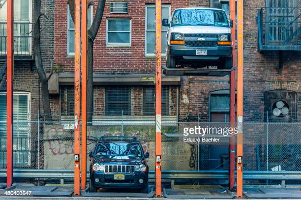 Two cars one on the base one lifted in a New York backyard carpark