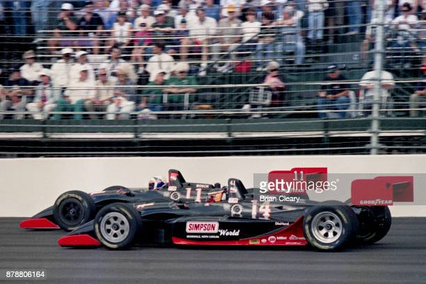 Two cars owned by IndyCar racing legend A J Foyt Jr the Lola Cosworth of Davey Hamilton and the Lola Cosworth of Mike Groff race side by side during...