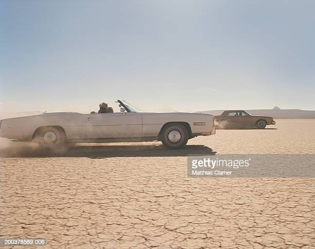 two cars racing in desert, side view - chasing stock pictures, royalty-free photos & images