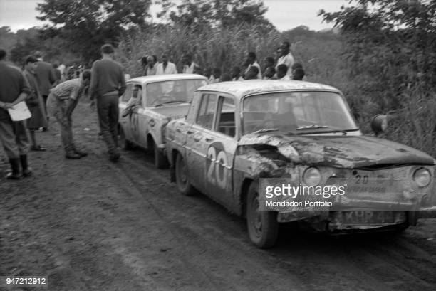Two cars running the East African Safari Rally waiting to start again Kenya April 1965
