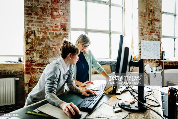 Two casual businesswomen working on computer