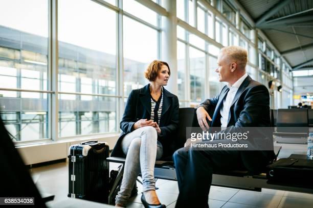 two casual mature business people talking at the airport - côte à côte photos et images de collection