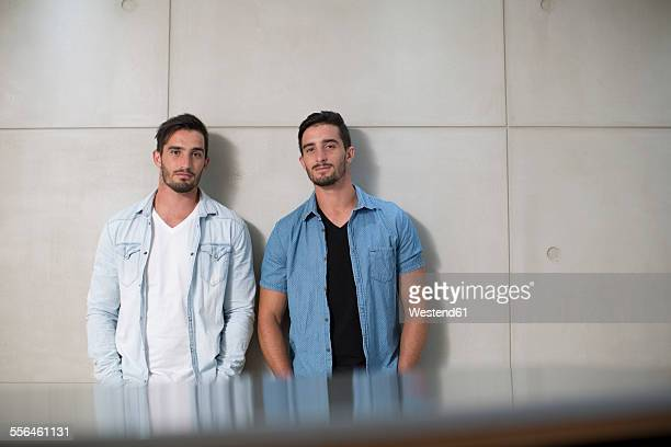 two casually dressed twin males in office - bruder stock-fotos und bilder