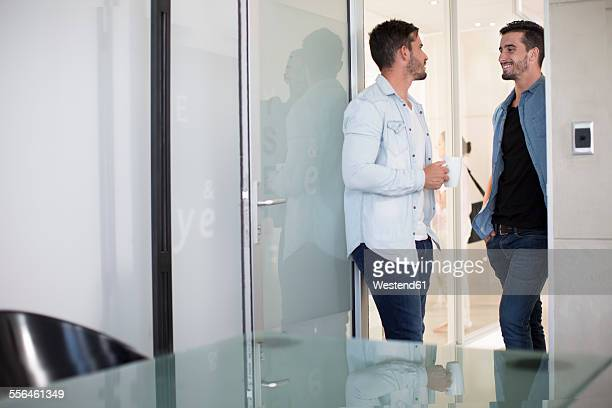 Two casually dressed twin males in office talking