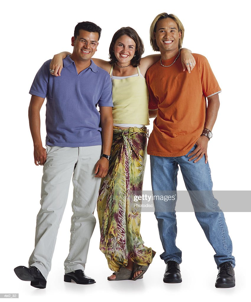 two casually dressed young men and a young woman are standing together with the woman in the middle and thier arms around each other smiling at the camera : Foto de stock