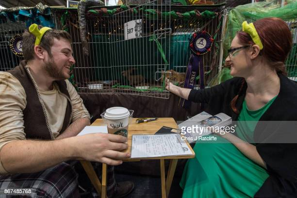 Two cat owners sit in front of their Shrek themed cat cage as they drink coffee with 'Sherk' written on the cup during the Supreme Cat Show on...