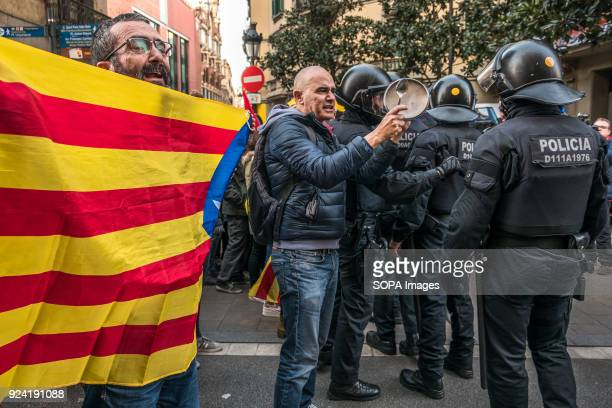 Two Catalan supporters seen carrying flags and banging pots in front of the police cordon against the presence of the King Felipe VI in Barcelona...